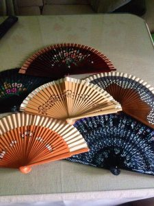 Seis abanicos abiertos, cuatro en color madera de diferentes tonalidades y dos negros