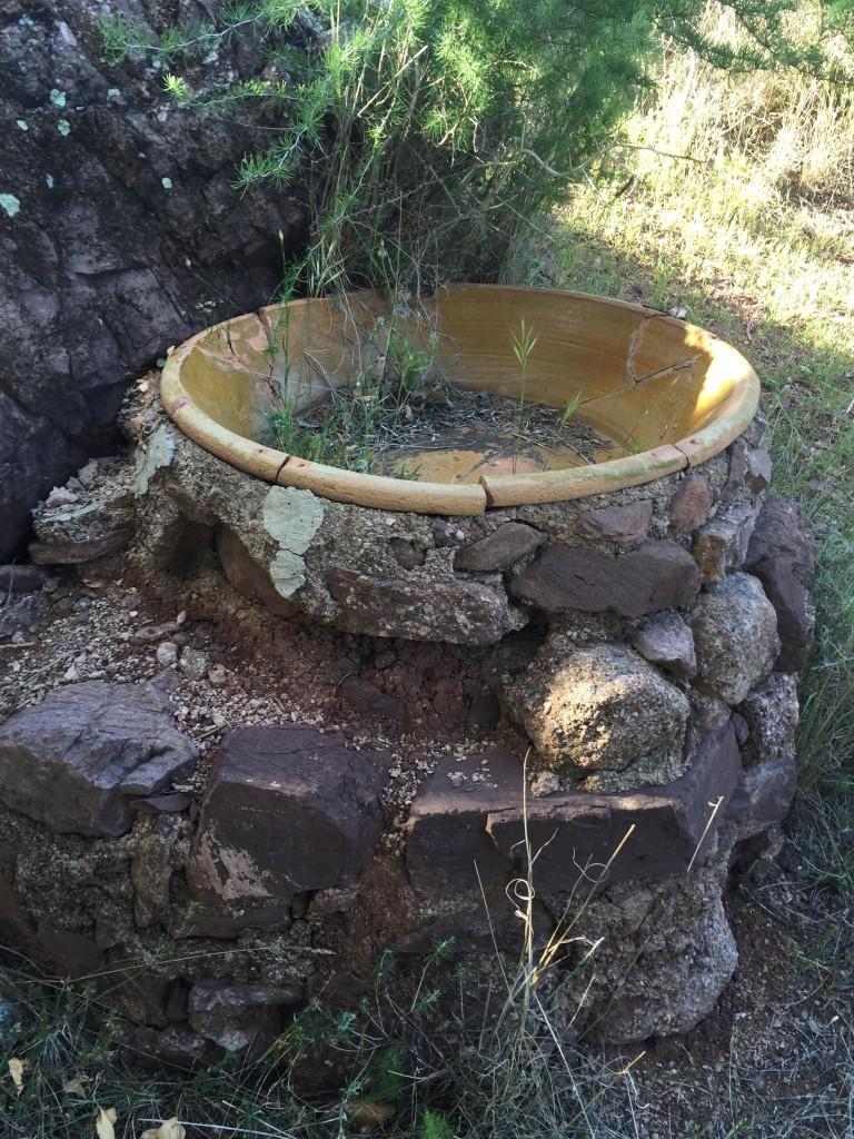 Lebrillo de cerámica sobre una base de piedras en el campo, junto a un pozo de agua