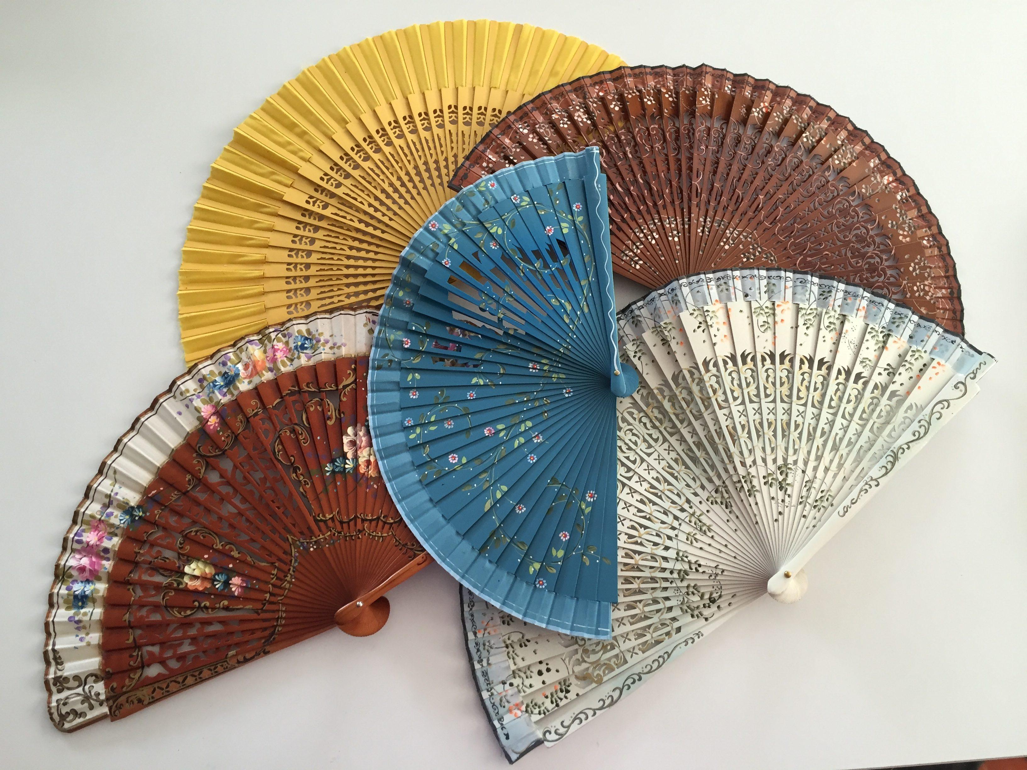 Cinco abanicos abiertos, dos en color madera, uno en azul, uno blanco y otro amarillo